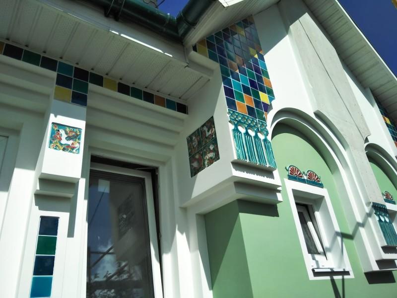 Рельефные кисти и изразцы из каменной массы на фасаде дома