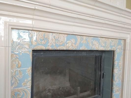 Камин в стиле бидермейер, облицованный кремовыми гладкими изразцами, рельефами акант и живописными вставками классических орнаментов